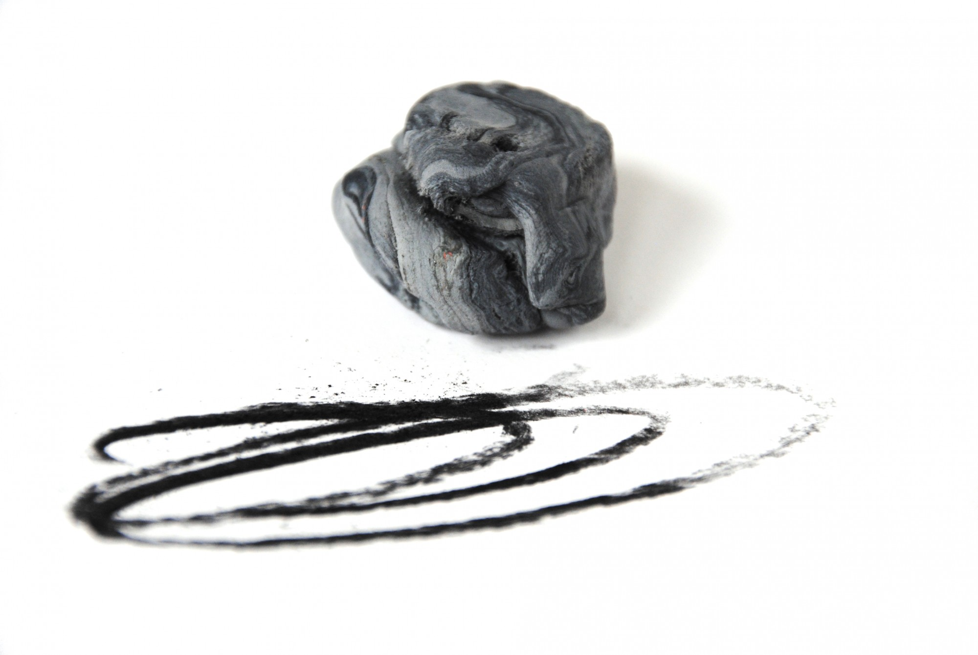 A piece of putty being used to absorb charcoal markings on paper.